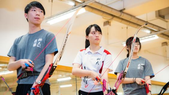 Edith practices archery with teammates regularly.