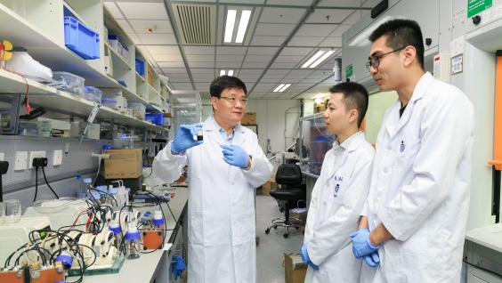 Prof. Zhao Tianshou (left) shows a sample of the e-fuel to his team members.