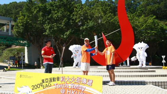 President Tony F Chan kicks off the torch relay by passing the torch to the first torch bearer.