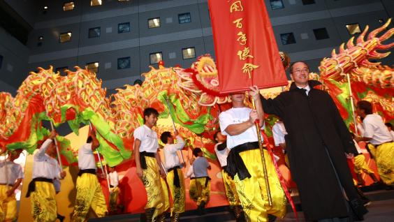 "President Tony F Chan with the Chinese slogan ""Great Vision for New Era"" at the end of the Dragon Dance."