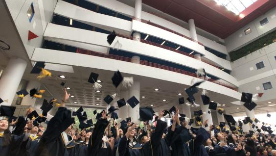 Graduates toss their hats in jubilation as the Congregation concludes.