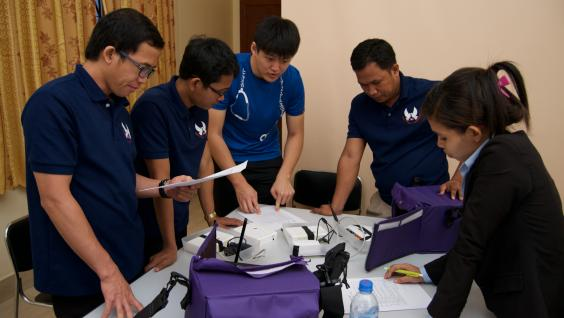 The student is demonstrating to the clinical staff in Cambodia how to use the mobile application of the electronic medical record system.